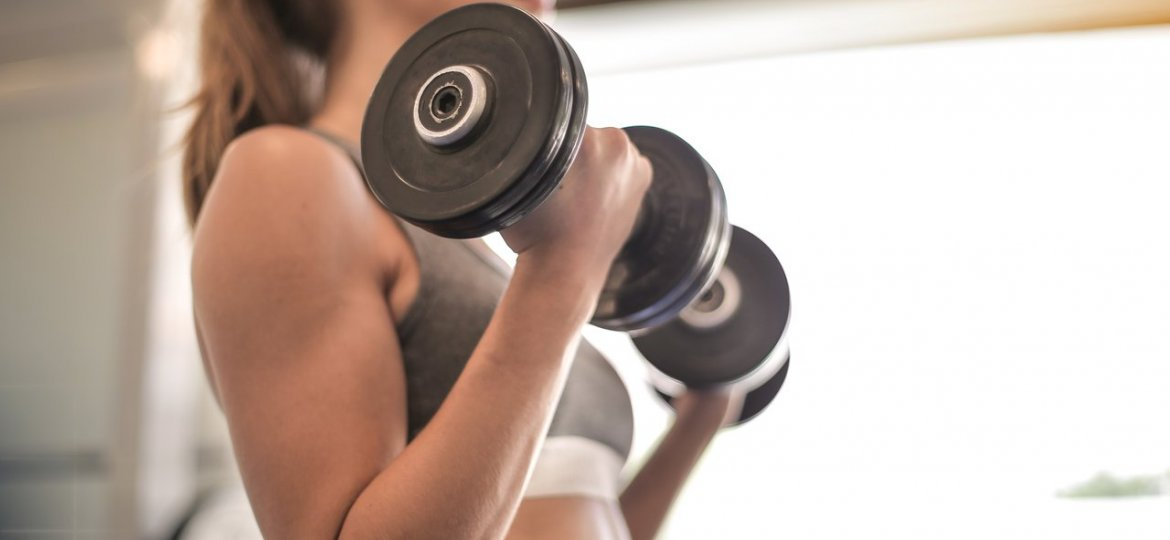 woman holding black dumbbell weight training
